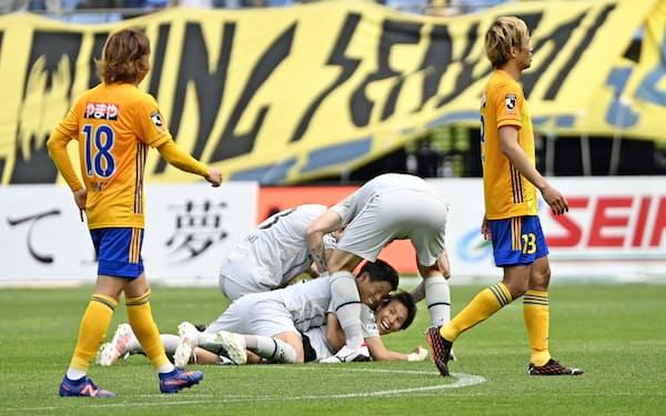 仙台―福岡 試合終了間際、決勝ゴールが決まり、祝福される福岡・渡=下(15日、ユアスタ)=共同