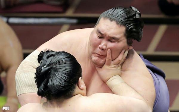 阿武咲(手前)の攻めをこらえる照ノ富士。寄り切りで下す(20日、両国国技館)=共同