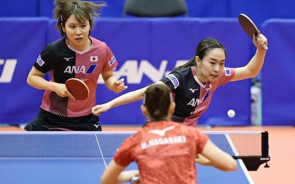 女子団体 第1試合のダブルスでフォアハンドショットを放つ石川。左は平野(3日、埼玉県内)=共同