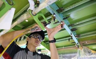 補強材を機体の骨組みに固定するため、リベットを通す穴を一つ一つドリルで開けていく