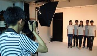 プロが使うスタジオでプロモデルを被写体に撮影するアマチュアカメラマンの竹内正人さん(手前)。「景気動向や流行などを基に、需要のある写真を撮るのが売れるコツ」という