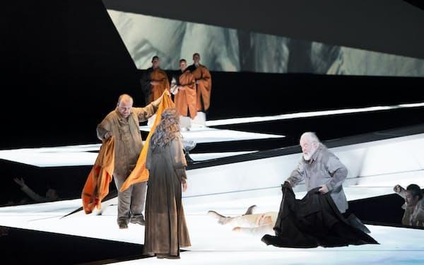 パルジファル(左)はクンドリー(中央後ろ向き)、グルネマンツ(右)に僧衣を分け与え、僧侶たちに導かれながら「光の道」へと歩み出す(撮影=寺司正彦、提供=新国立劇場)