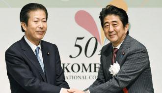 公明党の山口代表(左)と握手する安倍首相(9月21日、東京都港区)=共同