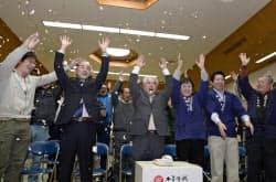 和紙がユネスコの無形文化遺産に登録され、「美濃和紙」の紙吹雪が舞う中で万歳する美濃市の武藤市長(前列左から3人目)ら(27日、岐阜県美濃市)=共同