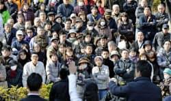 衆院選立候補者を応援する政党党首(手前右端)の演説を聞く有権者ら=6日午前、大阪府内