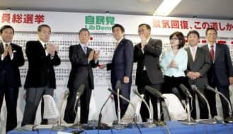 笑顔で当選のバラをつける安倍首相ら(14日、自民党本部)