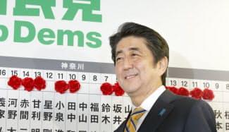 当選のバラの前で笑顔の安倍首相(14日夜、自民党本部)