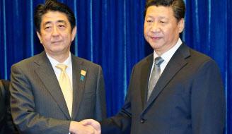 安倍晋三首相(左)と習近平国家主席の初会談は25分間だった(2014年11月10日)=共同