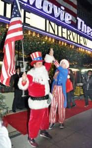 25日、米ロサンゼルスの映画館「シネファミリー」前で、星条旗を掲げる同館取締役のオーンスティンさんら=共同