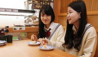 すしとデザートを食べる女子高生(東京都豊島区のくら寿司)