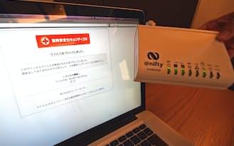 ルーターに専用のアダプター(右)をつないで使う。ウイルスを検知すると画面で知らせる