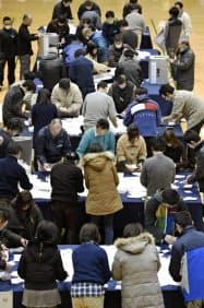 市立小中学校へのエアコン設置の是非を問う住民投票で、開票作業をする人たち(15日、埼玉県所沢市民体育館)=共同