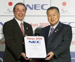 2020年東京五輪・パラリンピック組織委員会と「ゴールドパートナー」の契約を結び、調印書を手にするNECの遠藤信博社長(左)と組織委の森喜朗会長(19日、東京都港区)=共同