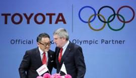 IOCのスポンサーに決まり、笑顔を見せるトヨタ自動車の豊田章男社長(左)と国際オリンピック委員会(IOC)のバッハ会長(13日午後、東京都千代田区)