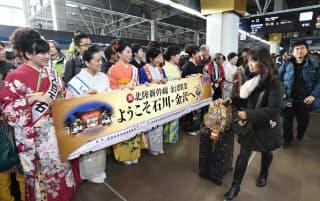 加賀友禅などの和服姿の女性らの出迎えを受ける、東京発一番列車の乗客(14日午前、JR金沢駅)