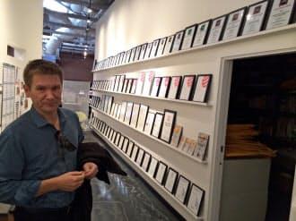 獲得した数々のデザイン賞の前に立つ著名デザイナーのダン・ハーデン氏