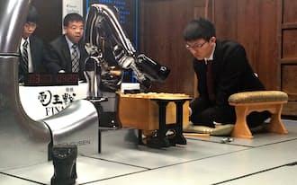 盤上をにらむ永瀬六段(手前はソフト側の駒を動かすロボット)