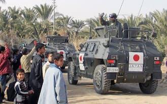 イラクのサマワ市内で、子どもたちに手を振る陸上自衛隊員(2005年1月)=共同
