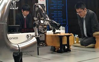 盤上を見つめる稲葉七段(左はソフト側の駒を動かすロボット)