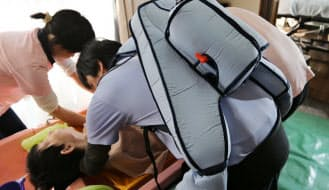 「マッスルスーツ」を装着して高齢者の入浴を手助けする介護スタッフ(川崎市)