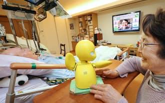 ロボットの「オリヒメ」(中央)を使って妻、裕子さん(右)と会話する藤沢義之さん