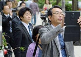 大阪府議選、市議選が告示され、政党の街頭演説を聞く人たち(3日、大阪市)=共同
