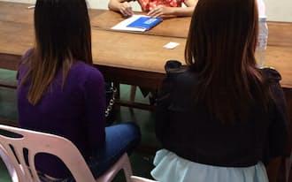 中国人男性と強制結婚させられたカンボジア人女性たち(手前)の話を非政府組織(NGO)の職員が聞き取りする(プノンペン)