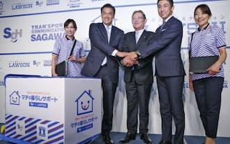 新会社「SGローソン」の設立を発表し握手するローソンの玉塚社長(左から2人目)、SGホールディングスの町田社長(同3人目)ら=7日午後、東京都港区