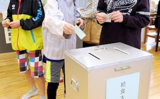 実際の投票箱などを使い模擬投票を行う小学6年生(6日、東京都多摩市の多摩第一小学校)