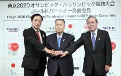 東京五輪・パラリンピックのスポンサーに決まり、握手する(左から)みずほフィナンシャルグループの佐藤社長、大会組織委員会の森会長、三井住友フィナンシャルグループの宮田社長(14日午後、東京都千代田区)