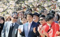「桜を見る会」で参加者と記念撮影に納まる安倍首相(18日午前、東京都新宿区の新宿御苑)
