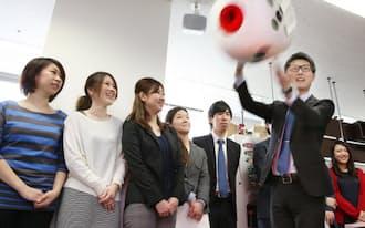 表彰金額を決めるためサイコロをふるエストコーポレーションの社員(東京都千代田区)