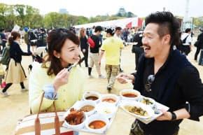 イベントで様々な種類のカレーを味わう人たち(大阪市中央区の大阪城公園)