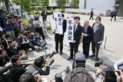 鹿児島地裁前で「不当決定」の垂れ幕を掲げる弁護団(22日午前、鹿児島市)