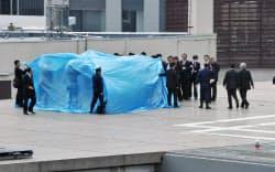 首相官邸の屋上で見つかった無人小型機・ドローンを調べる捜査員ら(22日、東京・永田町)