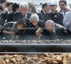 列車が衝突した跡が残るマンションで犠牲者の冥福を祈る人たち(25日午前、兵庫県尼崎市)