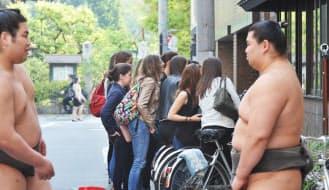 窓ガラス越しに朝稽古の様子を見学する外国人観光客(東京都中央区)