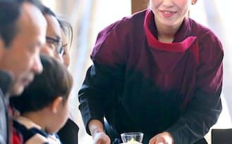 家族連れを接客する女性従業員(長野県軽井沢町の「星のや軽井沢」)