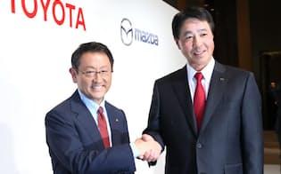 記者会見で握手するトヨタ自動車の豊田社長(左)とマツダの小飼社長(13日午後、東京都港区)