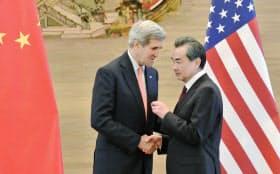 記者会見後に握手をしながら話し込むケリー米国務長官(左)と中国の王毅外相(16日、北京市内の中国外務省)