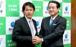 維新の党の両院議員総会で新代表に選出され、江田前代表(右)と握手する松野頼久氏(19日午後、国会内)