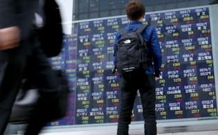 株価を見る男性(22日午後、東京・八重洲)
