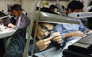 オークションに出品された中古ダイヤモンドを下見するインド人業者(東京都台東区)