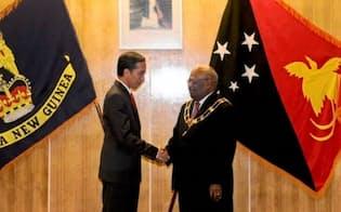 パプアニューギニアを訪問しオギオ総督(右)と握手するジョコ大統領(5月11日)