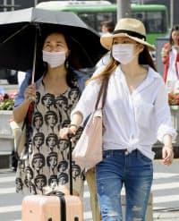 ソウル市内の観光地、東大門市場をマスク姿で歩く観光客(10日)=共同
