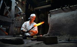 焼けた鉄のオレンジ色が、薄暗い工房に浮かび上がる