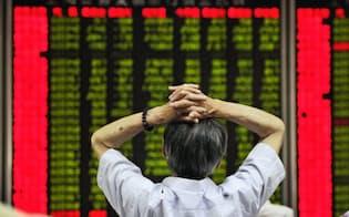 北京の証券会社で株価を示すボードを見る人=2日(共同)