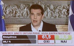 テレビを通じ勝利宣言するギリシャのチプラス首相(5日午後、アテネ市内のプレスセンター)=写真 浅原敬一郎