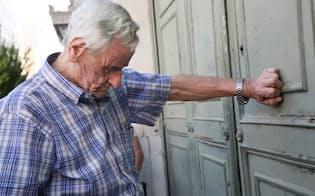 ATMカードを持たない年金受給者らのために特別に営業する銀行に並ぶ男性(7日午前、アテネ市内)=写真 浅原敬一郎
