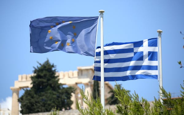 欧州旗(左)とギリシャの国旗。南欧国債の高利回りが注目されていたが。
